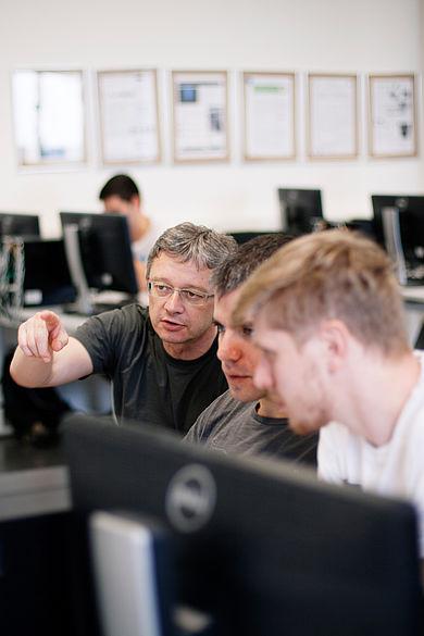 Professor erklärt Studierenden etwas am PC